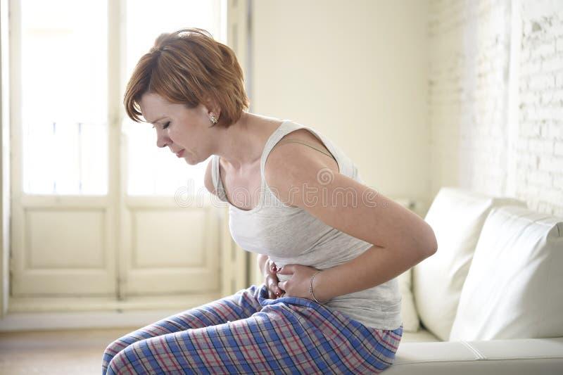 Menina no sofá do sofá que guarda o ferimento do grampo de estômago da barriga e da dor de sofrimento do período fotos de stock royalty free