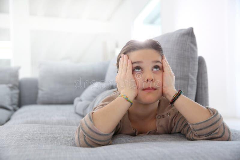 Menina no sofá que olha acima fotos de stock royalty free