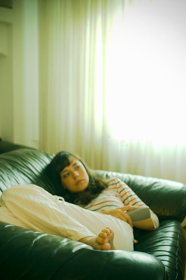 Menina no sofá que presta atenção à tevê