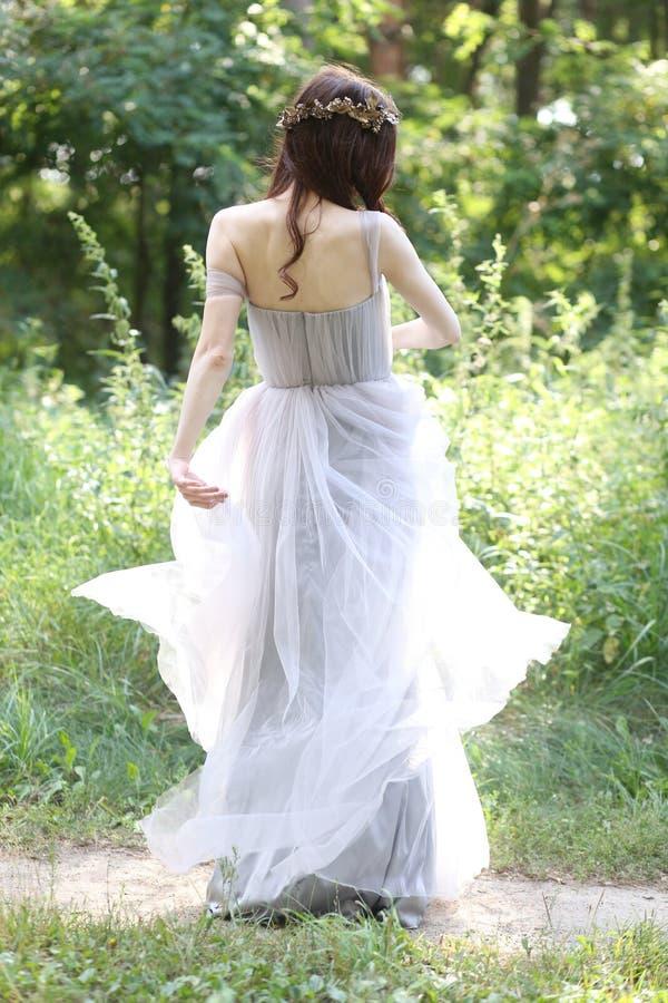 Menina no sol do trajeto das madeiras da dança do vestido fotos de stock royalty free