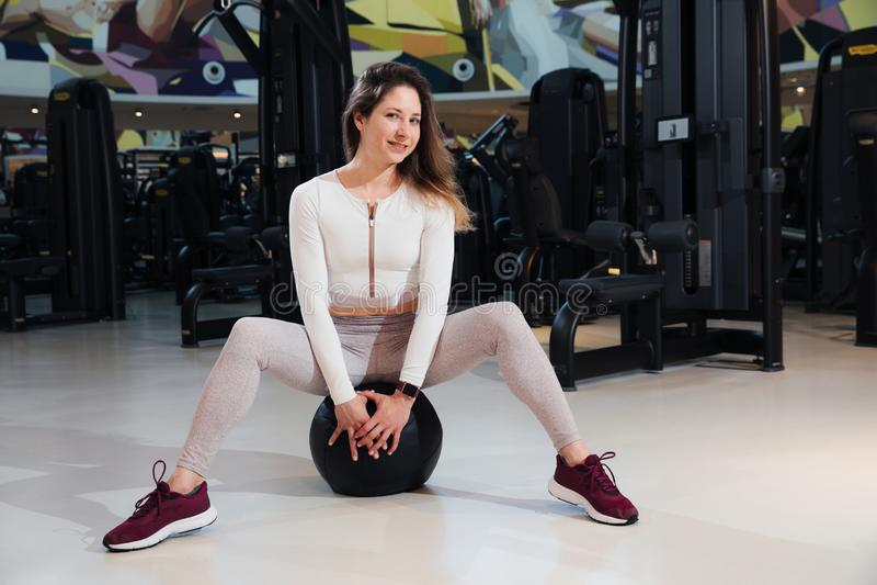 A menina no sportswear est? treinando no gym fotos de stock royalty free