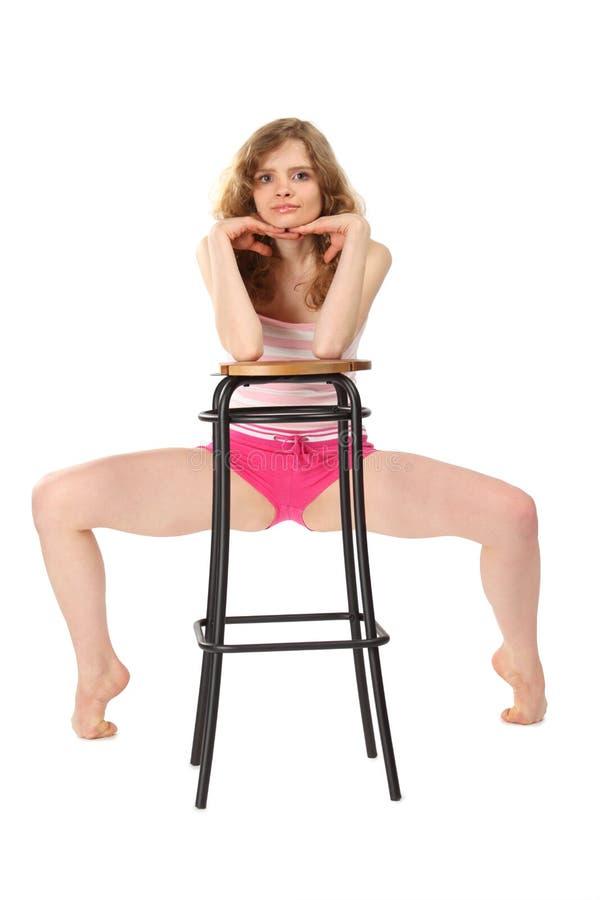 A menina no sportswear inclina-se de encontro ao tamborete de barra foto de stock royalty free