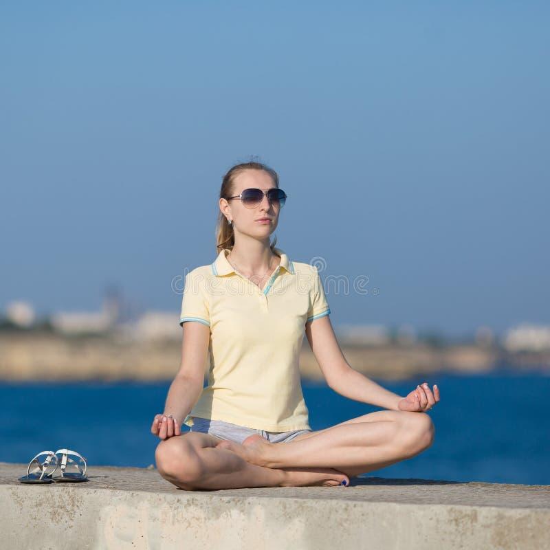 Menina no sportswear que senta-se na posição de metade-Lotus imagens de stock