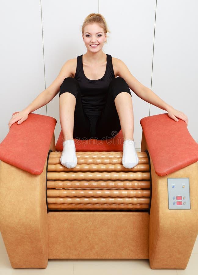 A menina no sportwear relaxa sobre o salão de beleza saudável dos termas do equipamento da massagem fotografia de stock