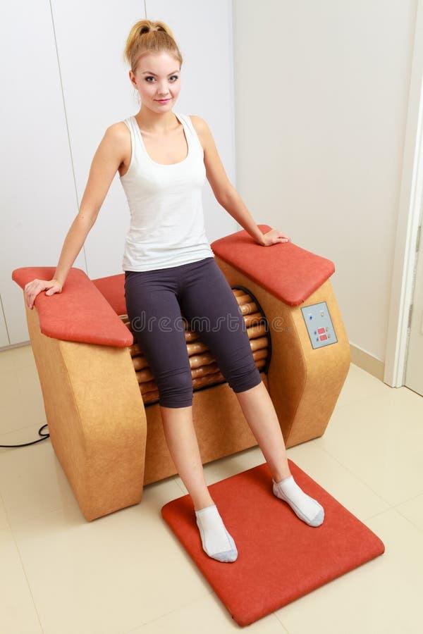 A menina no sportwear relaxa sobre o salão de beleza saudável dos termas do equipamento da massagem foto de stock royalty free