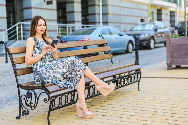 A menina no sundress senta-se em um banco imagens de stock royalty free