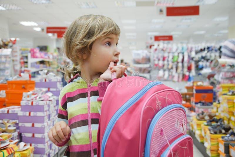 A menina no supermercado escolhe calçados fotografia de stock royalty free