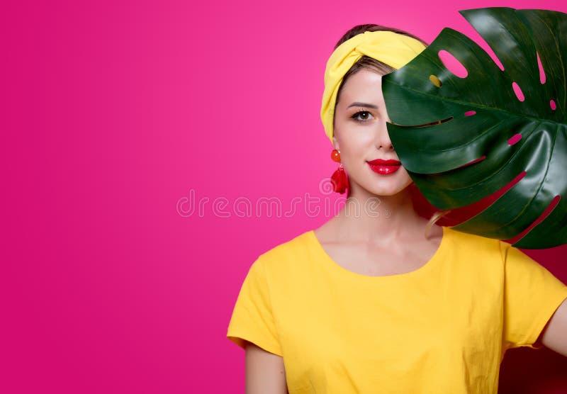 Menina no t-shirt amarelo perto da folha de palmeira fotos de stock royalty free