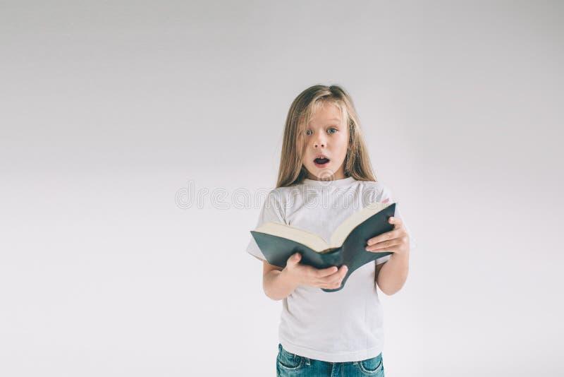 A menina no t-shirt branco está lendo um livro em um fundo branco A criança gosta de ler livros fotos de stock royalty free