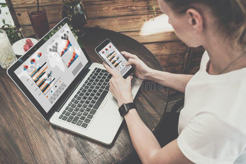 Menina no t-shirt branco que senta-se na tabela de madeira na cafetaria e que guarda o smartphone com tela vazia foto de stock royalty free