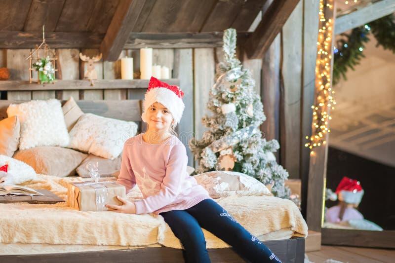 A menina no tampão de Santa Claus está esperando o ano novo na cama Menina no Natal com os presentes no quarto no s fotografia de stock royalty free