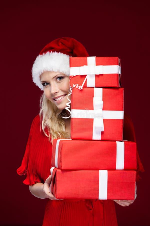 A menina no tampão do Natal entrega um jogo dos presentes imagem de stock royalty free