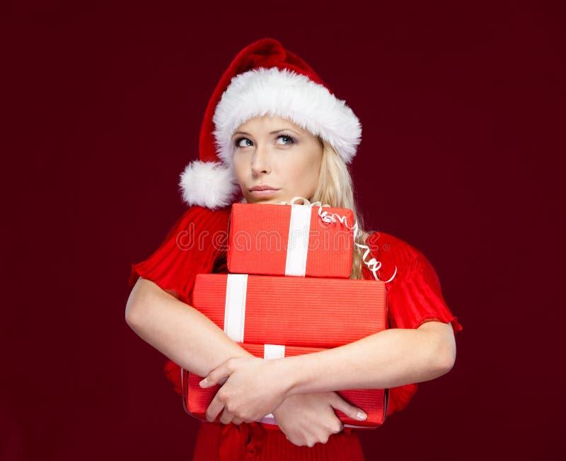A menina no tampão do Natal entrega um jogo dos presentes fotografia de stock royalty free