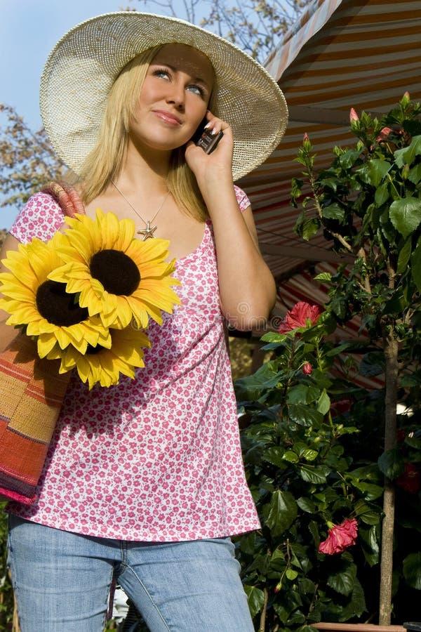 Menina no telefone de pilha com chapéu & girassóis de Sun imagens de stock