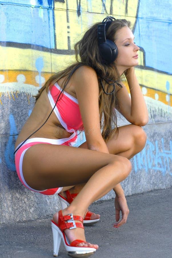A menina no terno de banho é música de escuta fotografia de stock