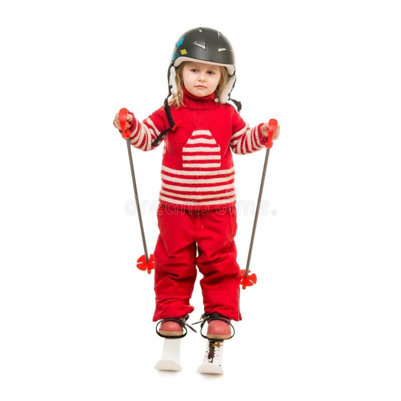 Menina no terno de esqui vermelho que está em esquis foto de stock