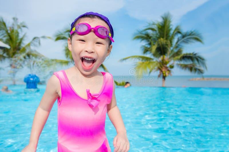 Menina no terno de nadada cor-de-rosa que sorri na piscina fotografia de stock
