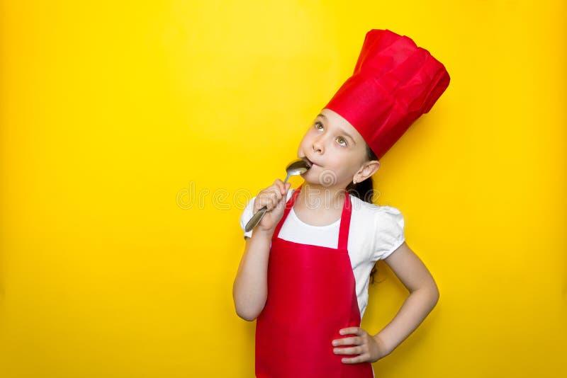 A menina no terno de um cozinheiro chefe vermelho lambe a colher, sonhos, gosto delicioso, no fundo amarelo com espaço da cópia fotografia de stock