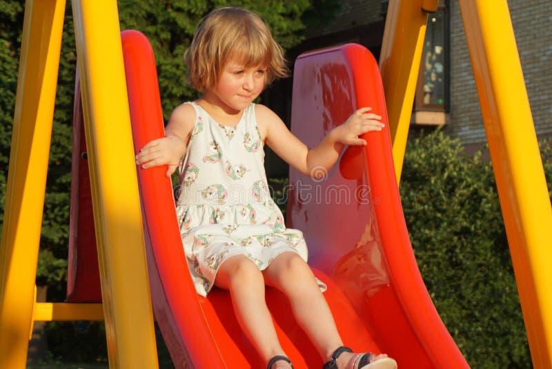 Menina no toboggan do campo de jogos com medo em seus olhos fotos de stock
