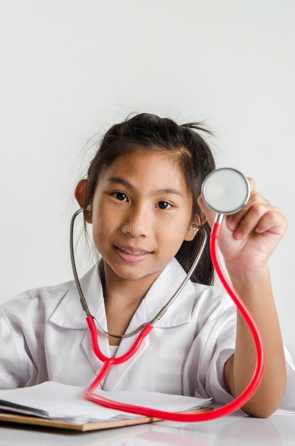 Menina no traje do doutor que guarda o estetoscópio vermelho no backgroun cinzento foto de stock