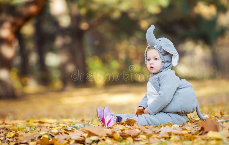 Menina no traje do elefante que joga na floresta do outono imagem de stock
