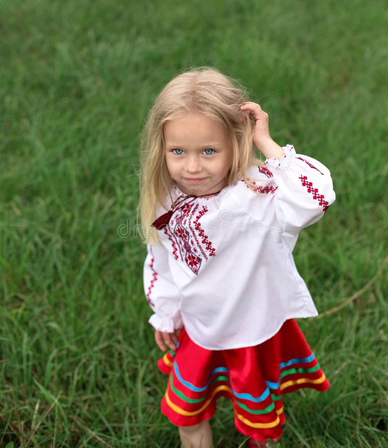 A menina no traje nacional ucraniano está jogando com seu h foto de stock