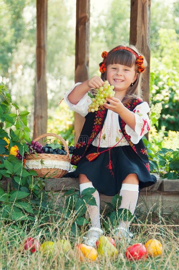 Menina no traje ucraniano nacional que senta-se no jardim com fruto foto de stock