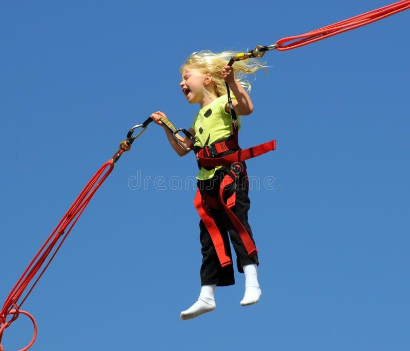 Menina no trampoline do tirante com mola foto de stock royalty free