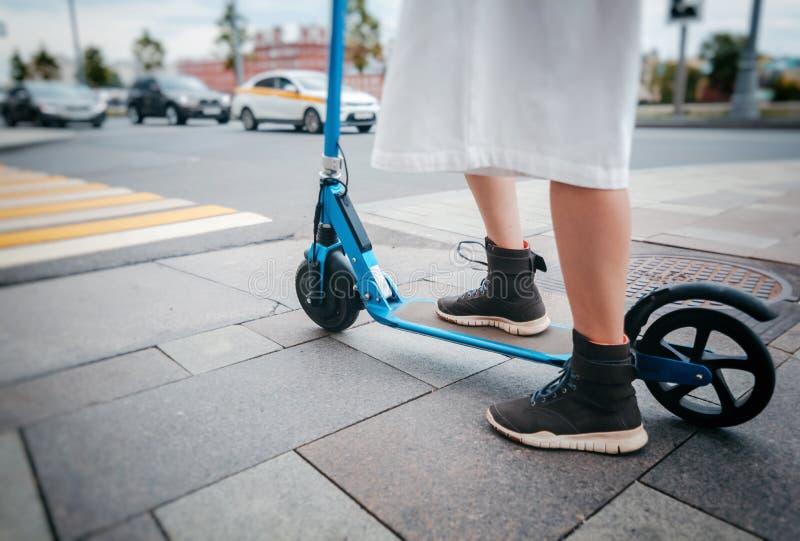 A menina no 'trotinette' elétrico do pontapé em um cruzamento pedestre, close-up dos pés imagem de stock