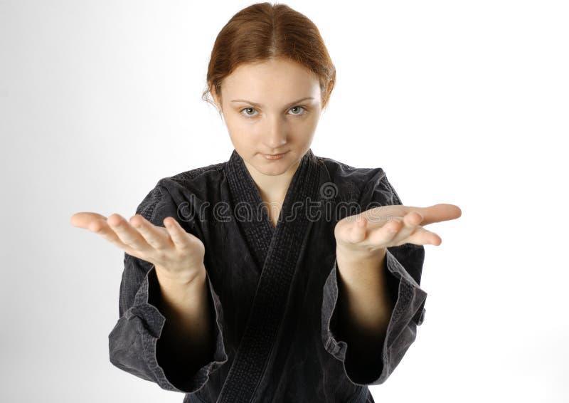 Menina no uniforme da arte marcial no fundo claro fotografia de stock