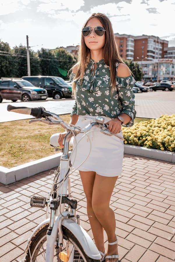 A menina no verão em suportes da cidade com uma bicicleta na cidade Blusa verde e short branco da saia Estilo de vida ativo foto de stock royalty free
