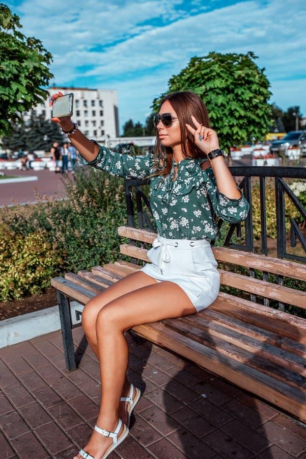 A menina no verão na cidade senta-se em um banco na cidade Óculos de sol, fotografias, chamada em linha ao Internet fotografia de stock royalty free
