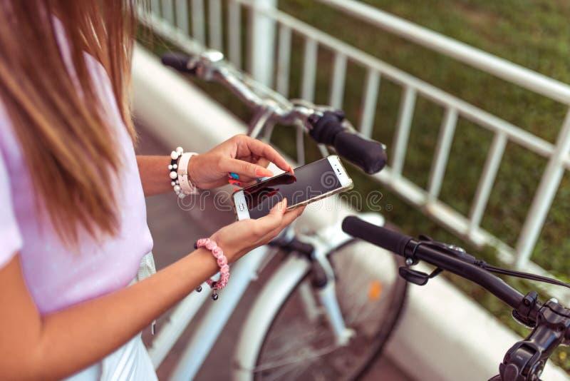Menina no ver?o no telefone disponivel da cidade, escolha da rota, fundo das bicicletas de estacionamento Candidatura online imagem de stock