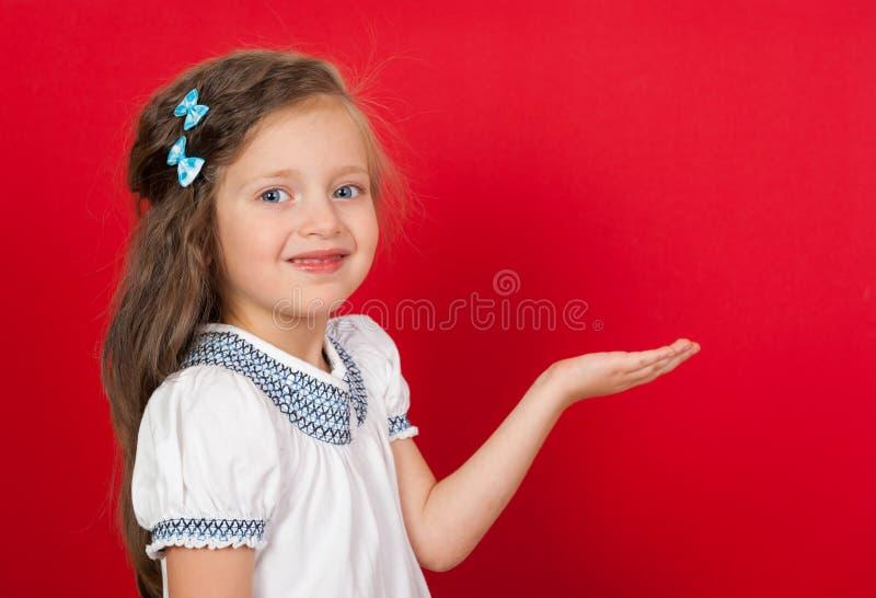 Menina no vermelho que mostra algo na palma fotografia de stock royalty free
