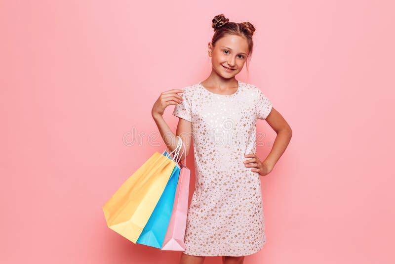 Menina no vestido à moda, adolescente com compras nas mãos, após a viagem de compra imagem de stock