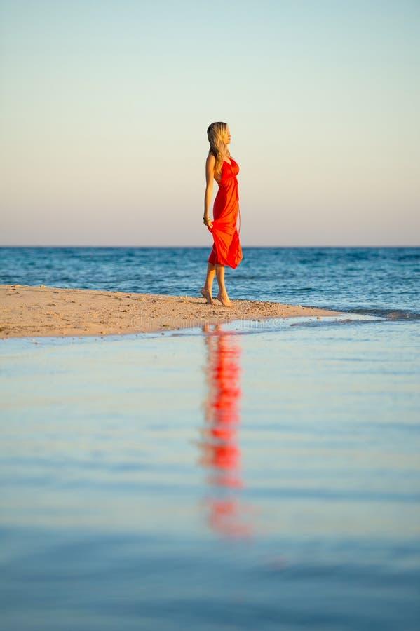 Menina no vestido alaranjado pela borda dos mares imagem de stock