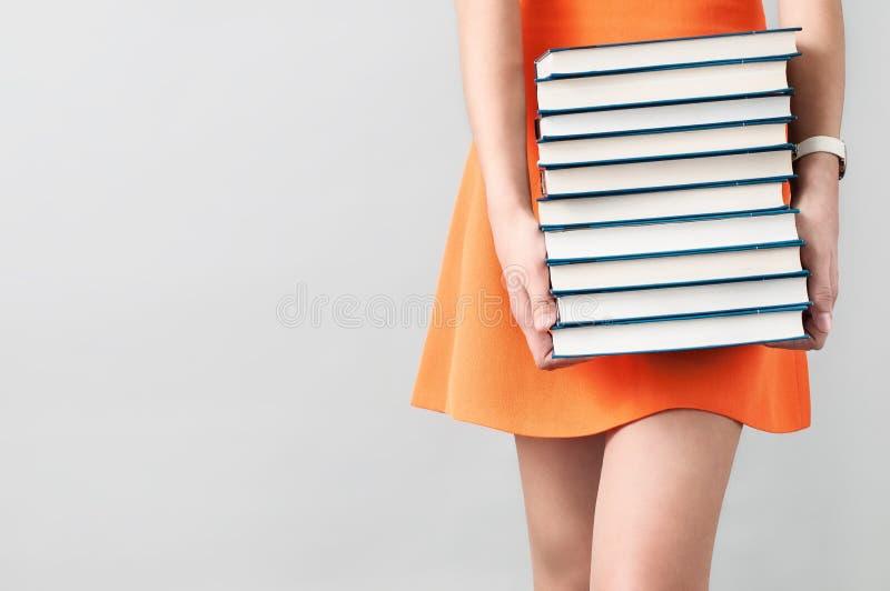 Menina no vestido alaranjado que guarda uma pilha de livros foto de stock royalty free