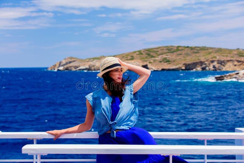 A menina no vestido azul e o chapéu têm uma viagem em um barco foto de stock
