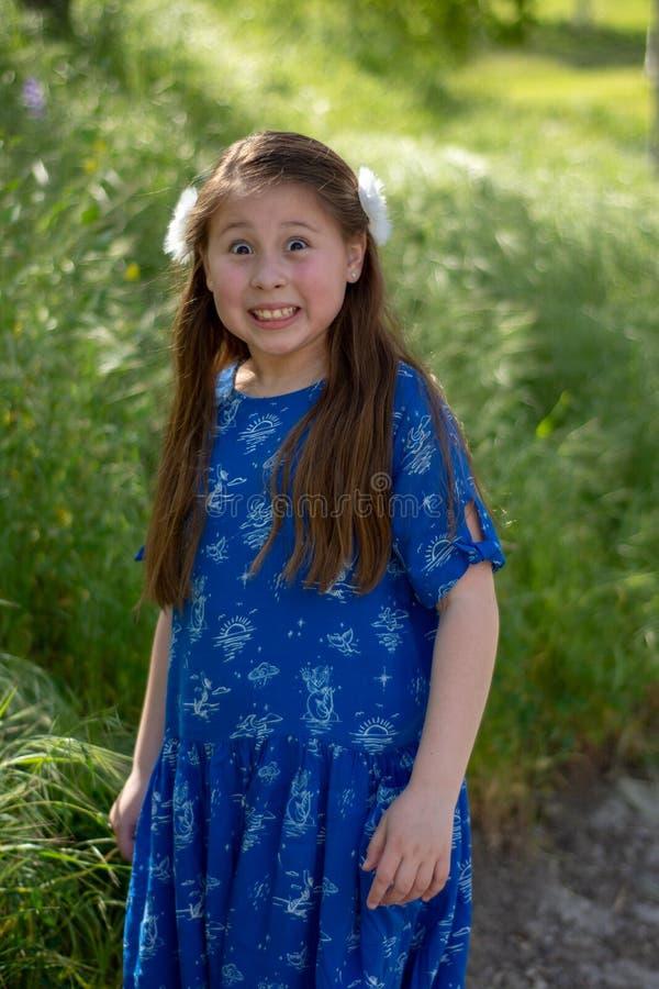 Menina no vestido azul que faz a cara engraçada e louca com língua para fora na frente do campo verde foto de stock royalty free