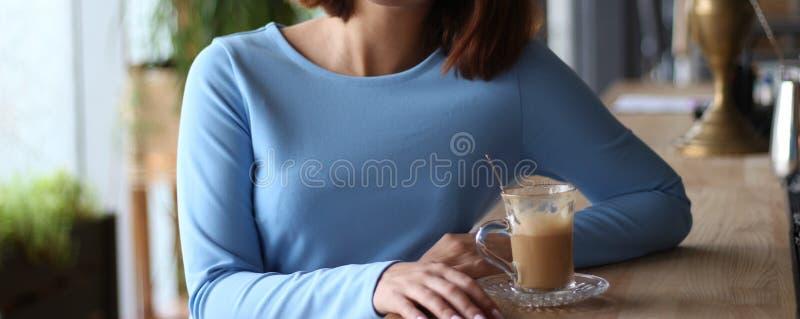 a menina no vestido azul senta-se em um contador da barra e bebe-se o café expectativa da reunião Café da manhã da manhã foto de stock royalty free