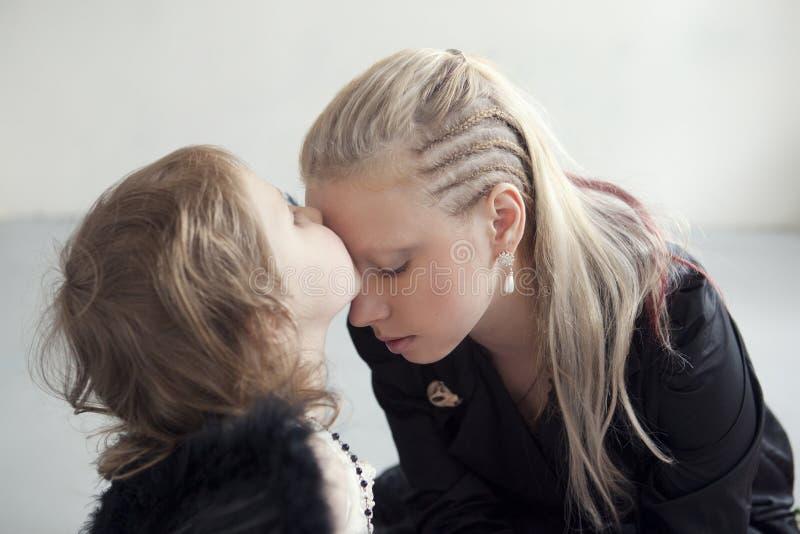 A menina no vestido branco com as asas pretas artificiais beija sua mãe na testa imagens de stock royalty free