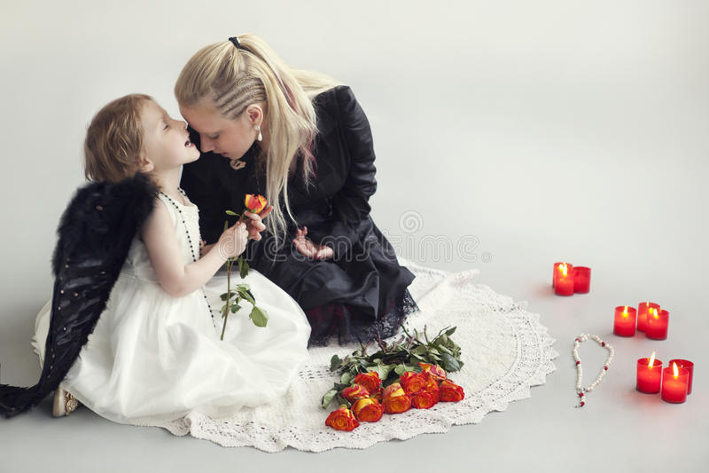 A menina no vestido branco com as asas pretas artificiais senta-se com a mamã no assoalho fotografia de stock