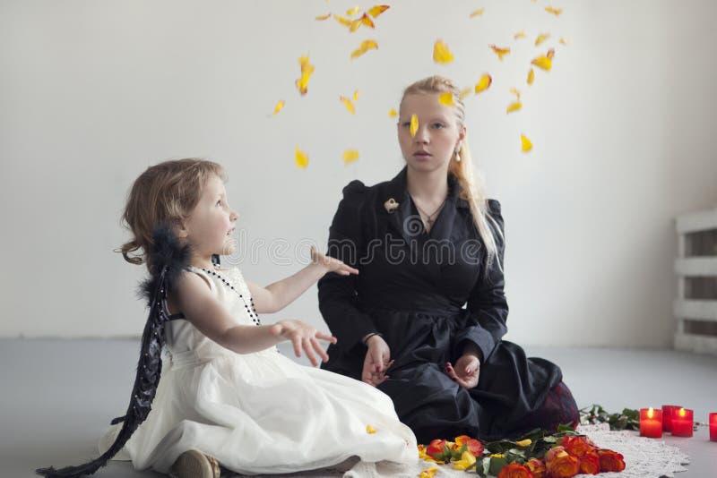 A menina no vestido branco com as asas pretas artificiais senta-se com a mamã no assoalho fotografia de stock royalty free