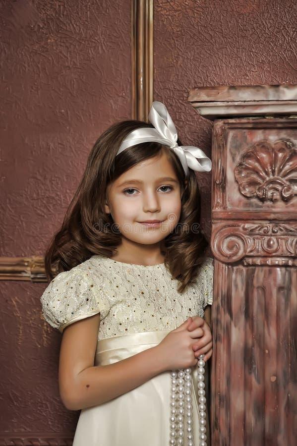 Menina no vestido branco com grânulos da pérola foto de stock royalty free