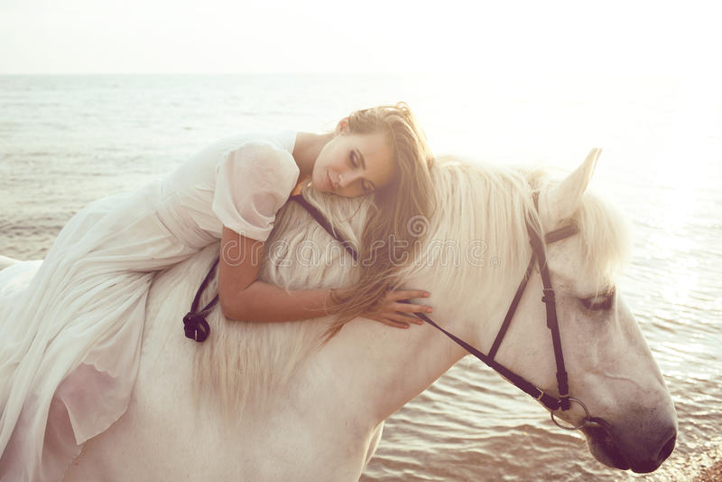 Menina no vestido branco com o cavalo na praia fotos de stock royalty free