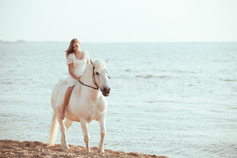 Menina no vestido branco com o cavalo na praia fotos de stock