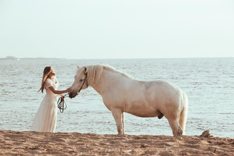 Menina no vestido branco com o cavalo na praia imagem de stock royalty free