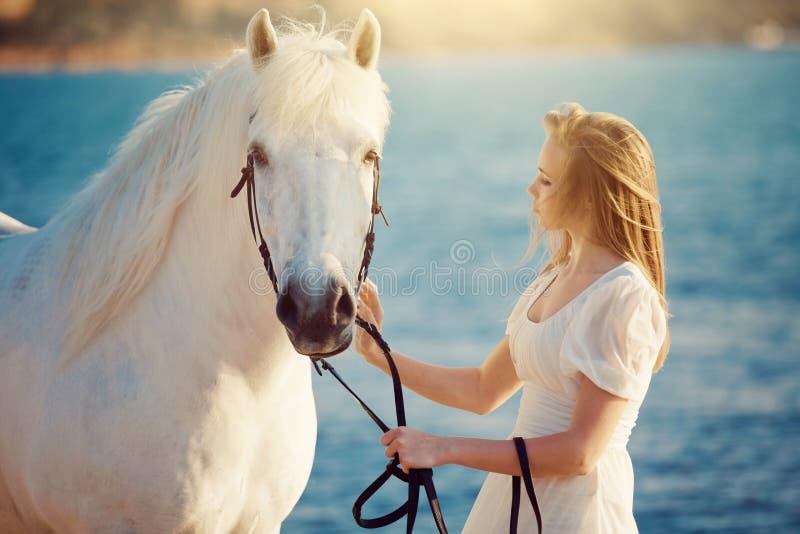 Menina no vestido branco com o cavalo na praia imagens de stock royalty free