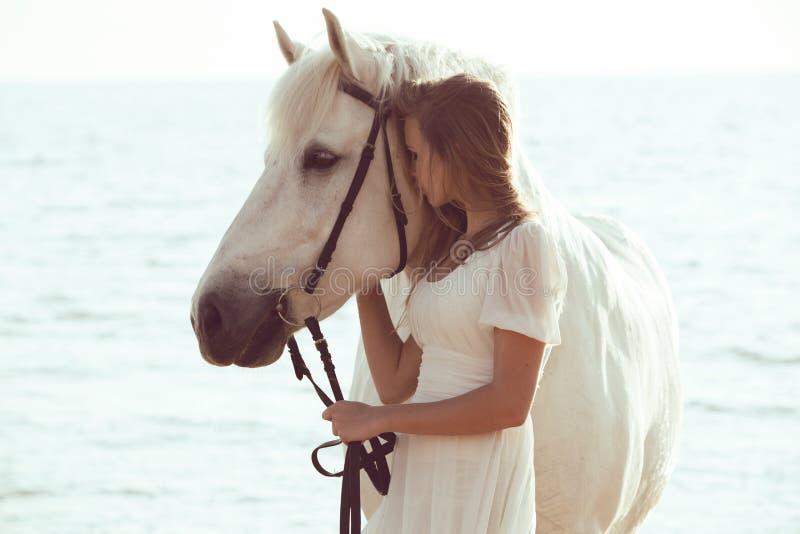 Menina no vestido branco com o cavalo na praia fotografia de stock royalty free
