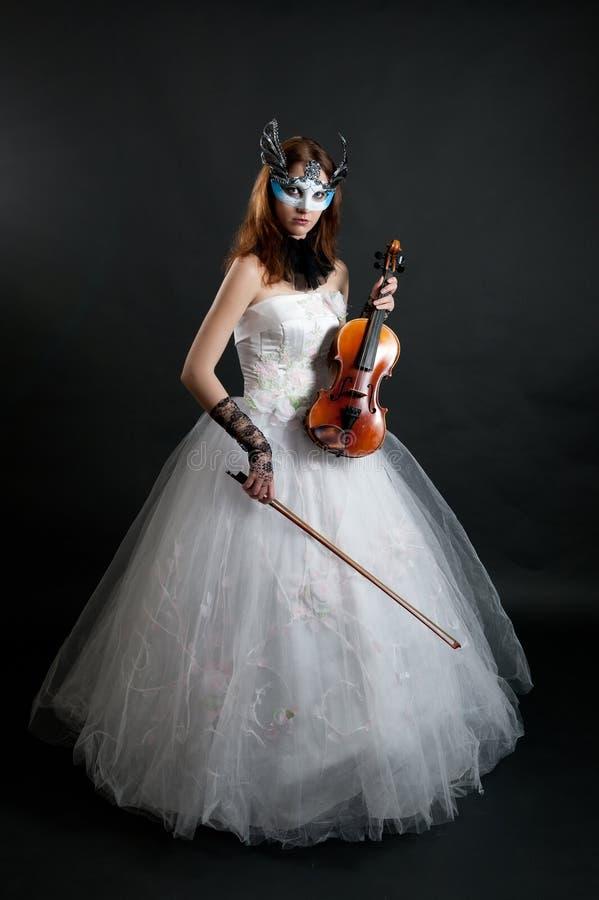 Menina no vestido branco e máscara com violino foto de stock